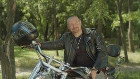Lifestyle portrait of biker sitting on motorcycle stock footage