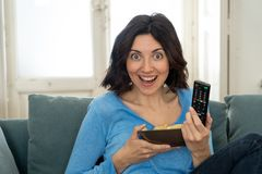 Lifestyle portrait of cheerful young woman sitting on the couch watching TV holding remote control royalty free stock image
