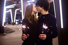 Lifestyle portrait of couple in love holding sparkling New Year fireworks on the city streets with lot of lights on background. Royalty Free Stock Images