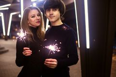 Lifestyle portrait of couple in love holding sparkling New Year fireworks on the city streets with lot of lights on background. Stock Photo