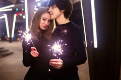 Lifestyle portrait of couple in love holding sparkling New Year fireworks on the city streets with lot of lights on background. Stock Image