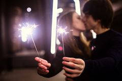 Lifestyle portrait of couple in love holding sparkling New Year fireworks on the city streets with lot of lights on background. Royalty Free Stock Photos