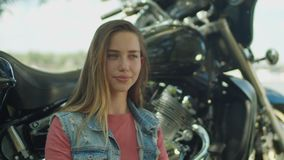 Lifestyle portrait of cute girl by motorcycle stock video