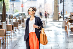 Lifestyle portrait of a french woman outdoors. Lifestyle portrait of a french woman walking with bag and baguette on the street with cafes in Lyon city Royalty Free Stock Photo