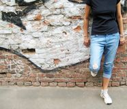 Lifestyle portrait of girl against colorful urban brick wall background. Lifestyle portrait of stylish young girl in casual clothes: black t-shirt, ripped jeans Royalty Free Stock Images