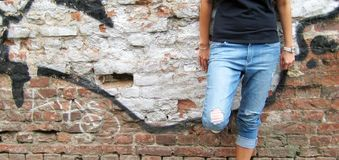 Lifestyle portrait of girl against colorful urban brick wall background. Lifestyle portrait of stylish young girl in casual clothes: black t-shirt, ripped jeans Royalty Free Stock Photography