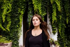 Lifestyle portrait of girl wearing blank black t-shirt, jeans and coat posing against building covered with green leaves. Minimalist urban clothing style Stock Images