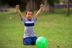 Lifestyle portrait at grass city park of 5 years old Asian kid playing football happy and excited raising arms celebrating scoring royalty free stock image