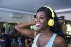 Lifestyle portrait at gym of young happy and attractive afro American woman training cheerful at fitness club listening to music w Stock Photography