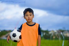 Lifestyle portrait of handsome and happy young boy holding soccer ball playing football outdoors at green grass field smiling chee. Rful wearing training vest in stock images