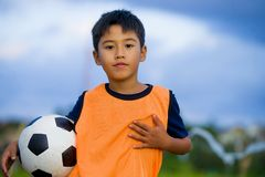 Lifestyle portrait of handsome and happy young boy holding soccer ball playing football outdoors at green grass field smiling chee. Rful wearing training vest in stock image