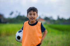 Lifestyle portrait of handsome and happy young boy holding soccer ball playing football outdoors at green grass field smiling chee royalty free stock photo