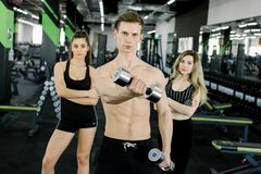 Lifestyle portrait of handsome muscular man with dumbbell in the gym. Young people training in the gym with barbells stock photos