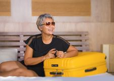 Lifestyle portrait of happy and attractive 40s to 50s mature Asian tourist woman with grey hair arriving in hotel room in business. Travel and explore . natural stock photos