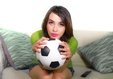 Young nervous and beautiful football fan woman watching television game sitting on sofa couch holding soccer ball excited highly c stock images