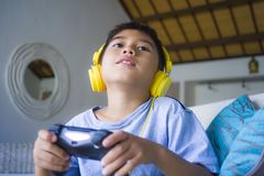 Latin young boy excited and happy playing video game online with headphones holding controller enjoying having fun sitting on couc stock photography