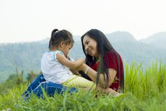 Lifestyle portrait mom and daughter in happiness at the outside in the meadow, Funny Asian family in a rice field royalty free stock photos