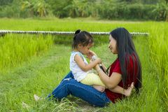 Lifestyle portrait mom and daughter in happiness at the outside in the meadow, Funny Asian family in a rice field royalty free stock images