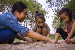 Lifestyle portrait mom son and daughter  playing with sand, Funny Asian family in a park stock photo