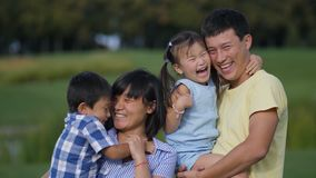 Excited asian family of four laughing in park stock footage
