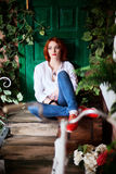 Lifestyle portrait of red head girl wearing blue jeans, white shirt and red shoes Royalty Free Stock Photography