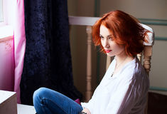 Lifestyle portrait of red head girl wearing blue jeans, white shirt and red shoes Stock Image