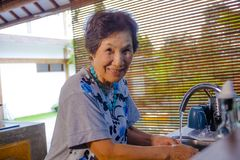 Lifestyle portrait of senior happy and sweet Asian Japanese retired, woman cooking at home kitchen alone neat and tidy. Washing the dishes smiling cheerful in stock images