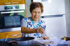 Lifestyle portrait of senior happy and sweet Asian Japanese retired woman cooking at home kitchen alone neat and tidy. Enjoying preparing meal in elderly and royalty free stock photos