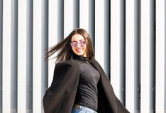 Lifestyle portrait of smiling young model in sunglasses with hair blowing in wind walking at the street. Lifestyle portrait of smiling young woman in sunglasses stock photo