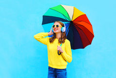 Lifestyle portrait smiling young woman listens to music in headphones with colorful umbrella in autumn day over colorful blue. Background wearing a yellow Royalty Free Stock Photo