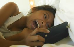 Lifestyle portrait of sweet happy and beautiful 7 years old child having fun playing internet game with mobile phone lying on bed royalty free stock images