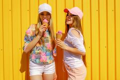 Lifestyle portrait of two beautiful best friend hipster lady wearing stylish bright outfits and having great time stock image