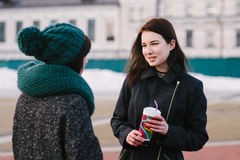 Lifestyle portrait of two female friends standing on the street and talking. Lifestyle portrait of two girls standing on the street and talking Royalty Free Stock Photo