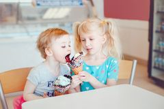 Funny children girls sitting together sharing ice-cream royalty free stock images