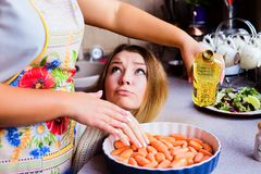 Lifestyle portrait of two happy young women cooking vegetables for Thanksgiving Dinner. One of them stealing food, concept of family eating and cooking Stock Photo