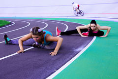 Lifestyle portrait of two young and athletic girls doing warm-up and workout and stretching Royalty Free Stock Photo