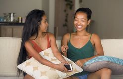 Lifestyle portrait of two young happy and relaxed Asian girlfriends having fun talking laughing and gossiping at home sofa couch s stock photography