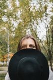Lifestyle portrait of woman covering half of her face with black hat stock photo