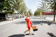 Woman crossing the street in Barcelona. Lifestyle portrait of a woman in red dress crossing the street at the modern district of Barcelona city Royalty Free Stock Photo