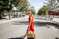 Woman crossing the street in Barcelona. Lifestyle portrait of a woman in red dress crossing the street at the modern district of Barcelona city Stock Photo