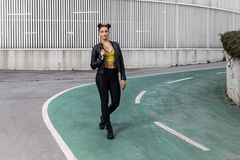 Lifestyle portrait of a woman wearing black leggings and leather jacket. Young woman wearing black leggings and leather jacket Stock Photography