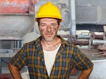 Young attractive and confident contractor or construction worker man with builder safety helmet posing corporate smiling cheerful royalty free stock photos