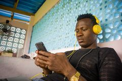 Lifestyle portrait of young attractive and cool hipster black afro American man using mobile phone and headset networking on stock photo