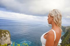 Young attractive and happy tourist woman looking the stunning view of beautiful sea cliff beach at viewpoint enjoying exotic. Lifestyle portrait of young stock photo
