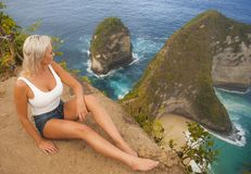 Young attractive and happy tourist woman looking the stunning view of beautiful sea cliff beach at viewpoint enjoying exotic. Lifestyle portrait of young royalty free stock photo