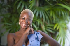 Lifestyle portrait of young attractive and joyful black afro american woman smiling happy posing cheerful at home terrace with gre. En plants background in royalty free stock image
