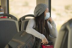 Lifestyle portrait of young attractive and pretty Asian woman wearing mask in railcar traveling in new normal virus time - sweet