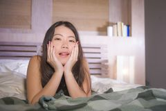 Lifestyle portrait of young beautiful and happy Asian Chinese woman lying in bed at home bedroom smiling cheerful and relaxed posi. Ng sweet and charming royalty free stock photo