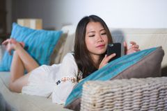 Lifestyle portrait of young beautiful and happy Asian Korean woman on her 20s or 30s lying at living room sofa couch using interne stock photography