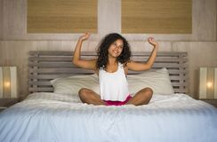 Lifestyle portrait of young beautiful and happy latin American woman waking up at home bedroom in the morning stretching arms on s royalty free stock photos